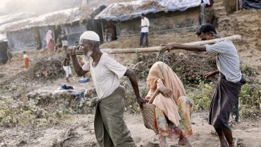 Family members carry a Rohingya woman suffering from a hip injury in a basket at a newly set-up refugee camp at Balukhali in Cox's Bazar, Bangladesh.