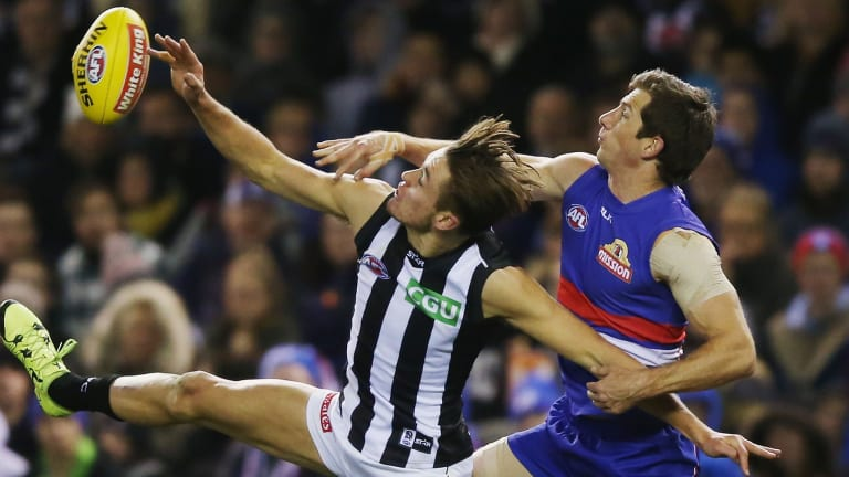 Darcy Moore competes for the ball against Dale Morris of the Bulldogs.