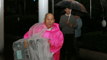 An electoral official transports a ballot box for the general election in the rain in Himeji, Hyogo, Japan, on Sunday.
