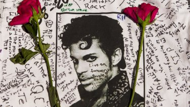 Flowers lie on a T-shirt signed by fans of singer Prince at a makeshift memorial place created outside Apollo Theatre in New York.