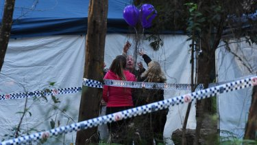 Mark Leveson (second from right) and Faye Leveson (right) release balloons with friends at the crime scene.