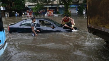 A man sits on a car that got stuck in a waterlogged street following heavy rains in Mumbai.