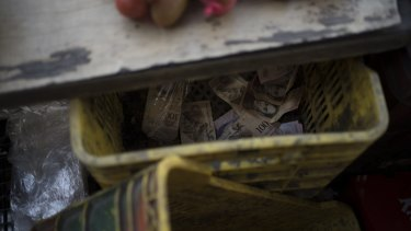A crate filled with 100-bolivar notes sits under the counter of a fruit stand in Caracas.