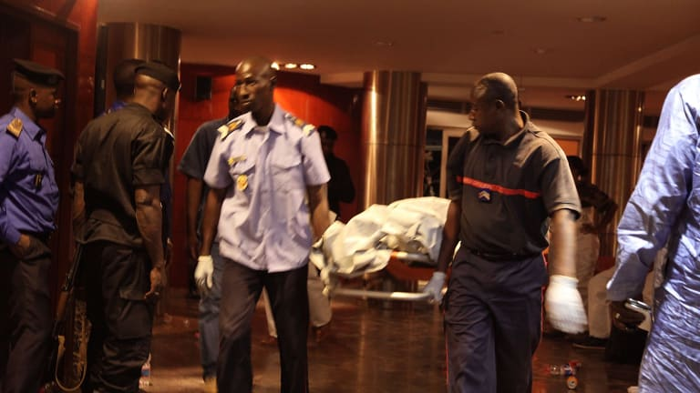 Mali security personnel remove the body of a victim from the Radisson Blu hotel after the attack that killed at least 21 people on Friday.