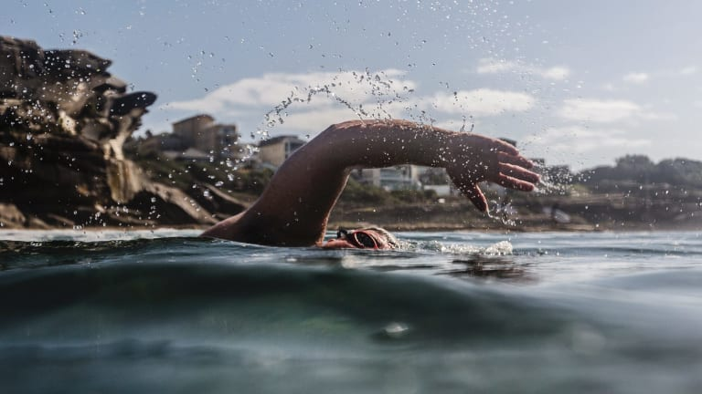 A swimmer enjoys the warm water at Tamarama on Monday.