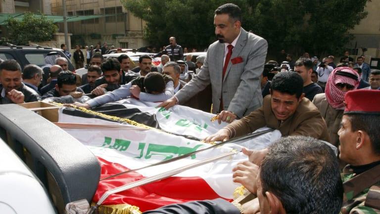 Men mourn during the funeral of  Iraqi Sunni leader Sheikh Qasim al-Janabi and his son Mohammad.