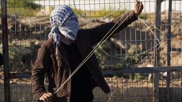 A Palestinian protester stretches a slingshot to hurl a stone during clashes with Israeli soldiers in the northern Gaza Strip on Friday.