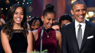 Malia and Sasha Obama with their father in Washington at Christmas,  2014.