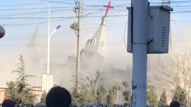 People watch the demolition of the Golden Lampstand Church in Linfen. Activists says the church had clashed with the government.