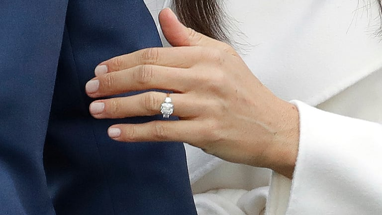 Britain's Prince Harry's fiancee Meghan Markle shows off her engagement ring.