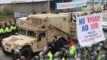 A US military vehicle in South Korea moves past protesters opposed to the THAAD missile defence system.