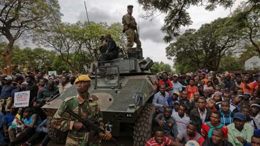 Army soldiers stand guard as protesters on Saturday demanded President Robert Mugabe stands down.