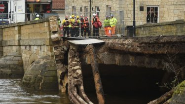 Emergency services check the collapsed bridge in Tadcaster, northern England, on Wednesday. Another storm was expected to hit many of the flood-affected areas of Britain the same day.