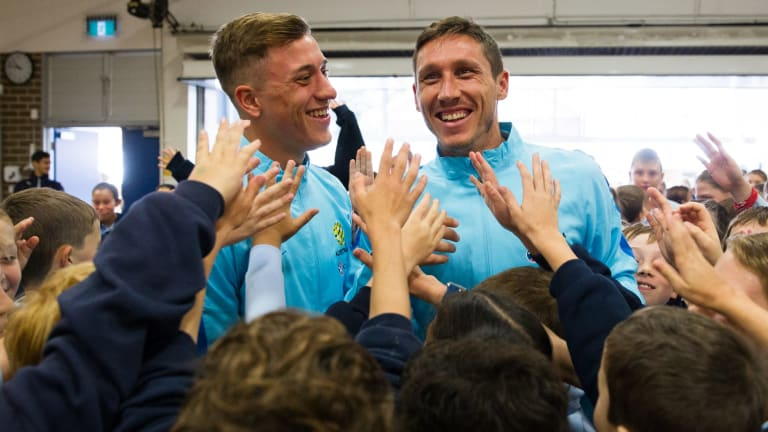 Kings of the kids: Socceroos Alex Gersbach and Mark Milligan with Double Bay Public School students on Wednesday.