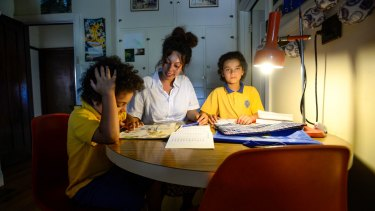 Leilani Landeryou and sons Rudy and Thomas doing their homework at the kitchen table.