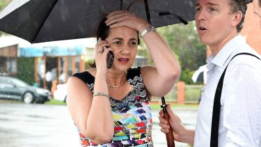 Queensland Premier Annastacia Palaszczuk is shielded from the rain by her media advisor as she takes a phone call.