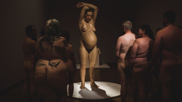 Art buffs take in Ron Mueck's 'Pregnant woman' at the National Gallery of Australia during a naked event at Hyper Real.