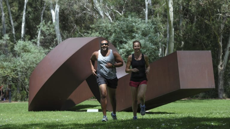 Lunchtime joggers, Link Perera of Kambah and Jodie Bijorac of Queanbeyan, run through the sculpture garden at the National Gallery of Australia. New figures show Canberra is the most active and cultured place in the country.