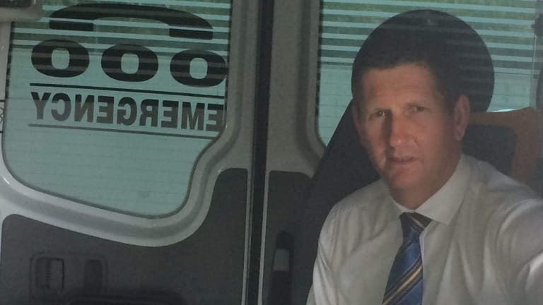 LNP leader Lawrence Springborg visits a Brisbane ambulance station, projecting business as usual while the state election outcome is decided.