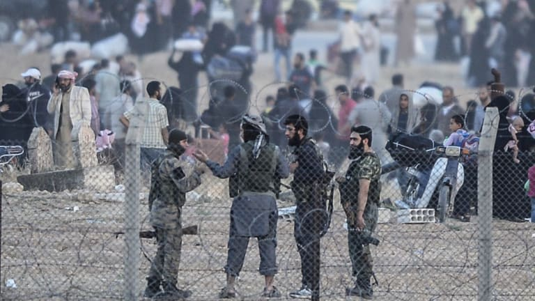 Islamic State fighters discuss the situation at the border fence. It is believed that 150 IS fighters are holding Tal Abyad against Kurdish militia and US-led air strikes.
