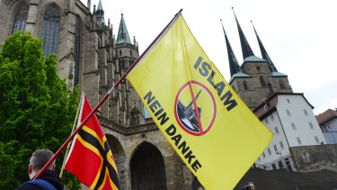 """A demonstrator carries a flag reading """"Islam, no thanks"""" during the Erfurt rally of Alternative for Germany."""