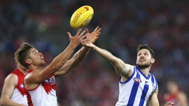 North Melbourne's Aaron Black competes for the ball with Sydney's Dane Rampe.