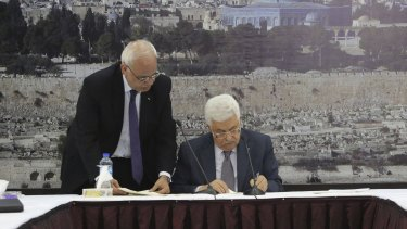 Palestinian Authority President Mahmoud Abbas (right) signs international agreements handed to him by chief Palestinian negotiator Saeb Erekat.