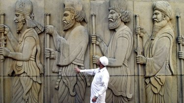 A Parsi priest reverently touches the statues, believed to be of ancestors, outside a Fire Temple in Mumbai, India.