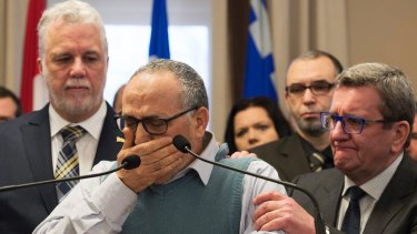 Mohamed Labibi, president of the Islamic cultural centre, is comforted by Quebec Premier Philippe Couillard, left, and Quebec City mayor Regis Labeaume, right.