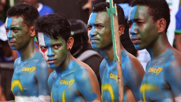 CNRT supporters  have their face and body painted with the party's colors during a campaign rally in Dili.