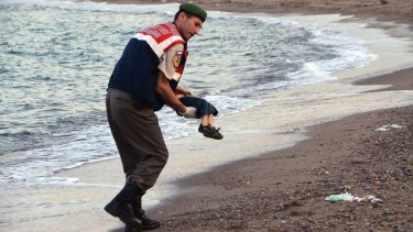 A police officer carries three-year-old Aylan Kurdi after he drowned near the Turkish resort of Bodrum.