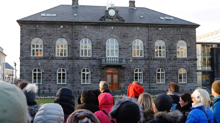 People stand outside the Icelandic parliament the Althing in Reykjavik. Iceland will be the first country in the world to make employers prove they offer equal pay regardless of gender, ethnicity, sexuality or nationality.