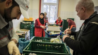 Nadja Haj Mohamad, centre, and other Germans sort through delivered food at the Tafel food bank headquarters in Bremerhaven, which has seen a sevenfold increase in the number of people served since Angela Merkel came to power.