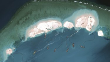A handout satellite image shows dredgers working at the northernmost reclamation site of Mischief Reef, part of the Spratly Islands, in the South China Sea, March 16, 2015.