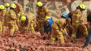 Firemen and workers dig through the debris after the wall collapse in March 2013.