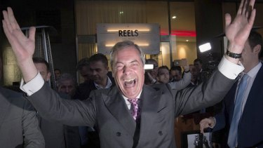 """Nigel Farage, the leader of the UK Independence Party, celebrates and poses for photographers as he leaves a """"Leave EU"""" party on Friday."""