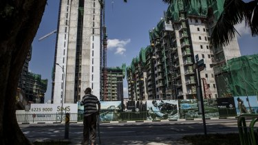 A man stands next to the Sims Urban Oasis condominium worksite in Singapore.