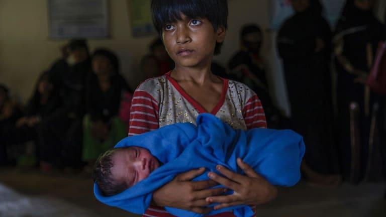 Rohingya Muslim girl Afeefa Bebi, who recently crossed over from Myanmar into Bangladesh, holds her few-hours-old brother as doctors check her mother Yasmeen Ara at a community hospital in Kutupalong refugee camp, Bangladesh on Wednesday.