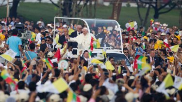 Pope Francis, standing at right on pope-mobile, greets Christians upon his arrival for a holy Mass in Yangon, Myanmar, on Wednesday.