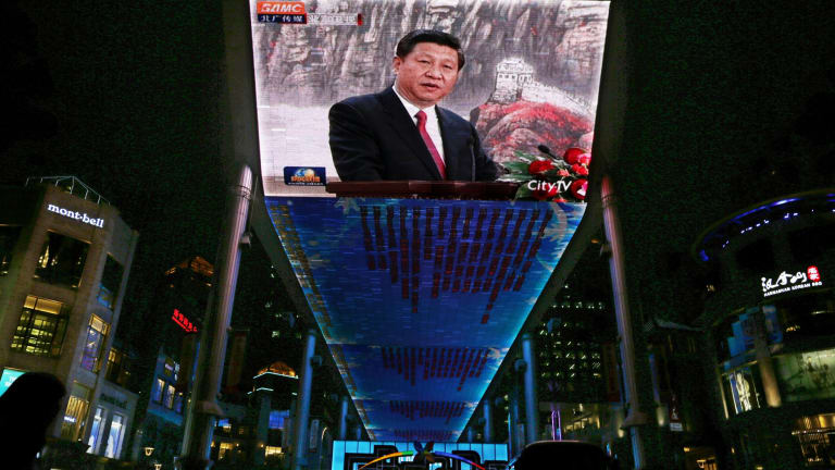 A huge screen shows a broadcast of  Xi Jinping speaking in Beijing's Great Hall of the People.