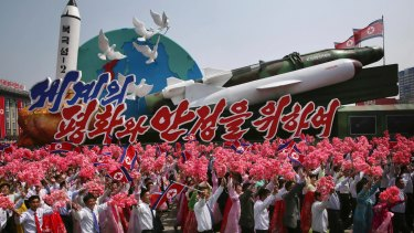 North Koreans wave as they march next to a float display of models of different missiles during a military parade in Pyongyang earlier this month.