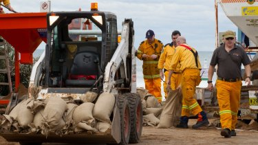 Workers commence a sandbagging operation on Tuesday to try to stop the collapse of an apartment building.