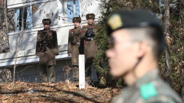 North Korean soldiers look at a South Korean guard standing near the spot where a North Korean soldier crossed the border in the Demilitarised Zone on November 13.