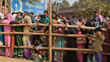 Indians stand in a queue to deposit and exchange discontinued currency notes outside a bank in Allahabad, India.