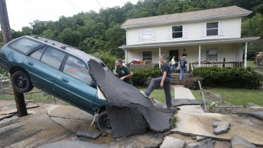 Jay Bennett, left, and step-son Easton Phillips survey the damage to a neighbors car in front of their home damaged by floodwaters as the cleanup begins from severe flooding in White Sulphur Springs, West Virginia.
