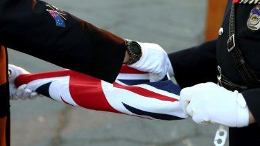 Australian police officers fold the Australian flag during a flag-lowering ceremony. in Nicosia, Cyprus.