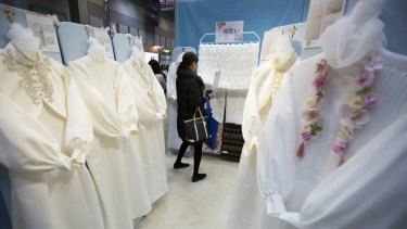 A shrinking population and longer hours for those left behind. An attendee looks at burial clothes displayed at the Life Ending Industry Expo in Tokyo, Japan.