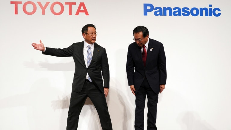 Toyota President Akio Toyoda, left, escorts Panasonic President Kazuhiro Tsuga, after they announced they are considering developing batteries for electric vehicles together.