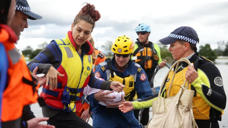 A young mother and her seriously ill four-month old baby are taken across the water in an inflatable boat.