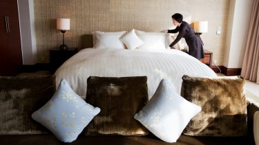 An employee arranges a bed inside a royal suite room at the Hotel Lotte Co. Seoul hotel in South Korea.